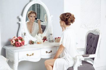 Young beautiful happy woman sitting in front of mirror and preparing to wedding. holding makeup brush and looking at herself. indoor studio shot. amazing bridal morning. wedding concept and feelings.