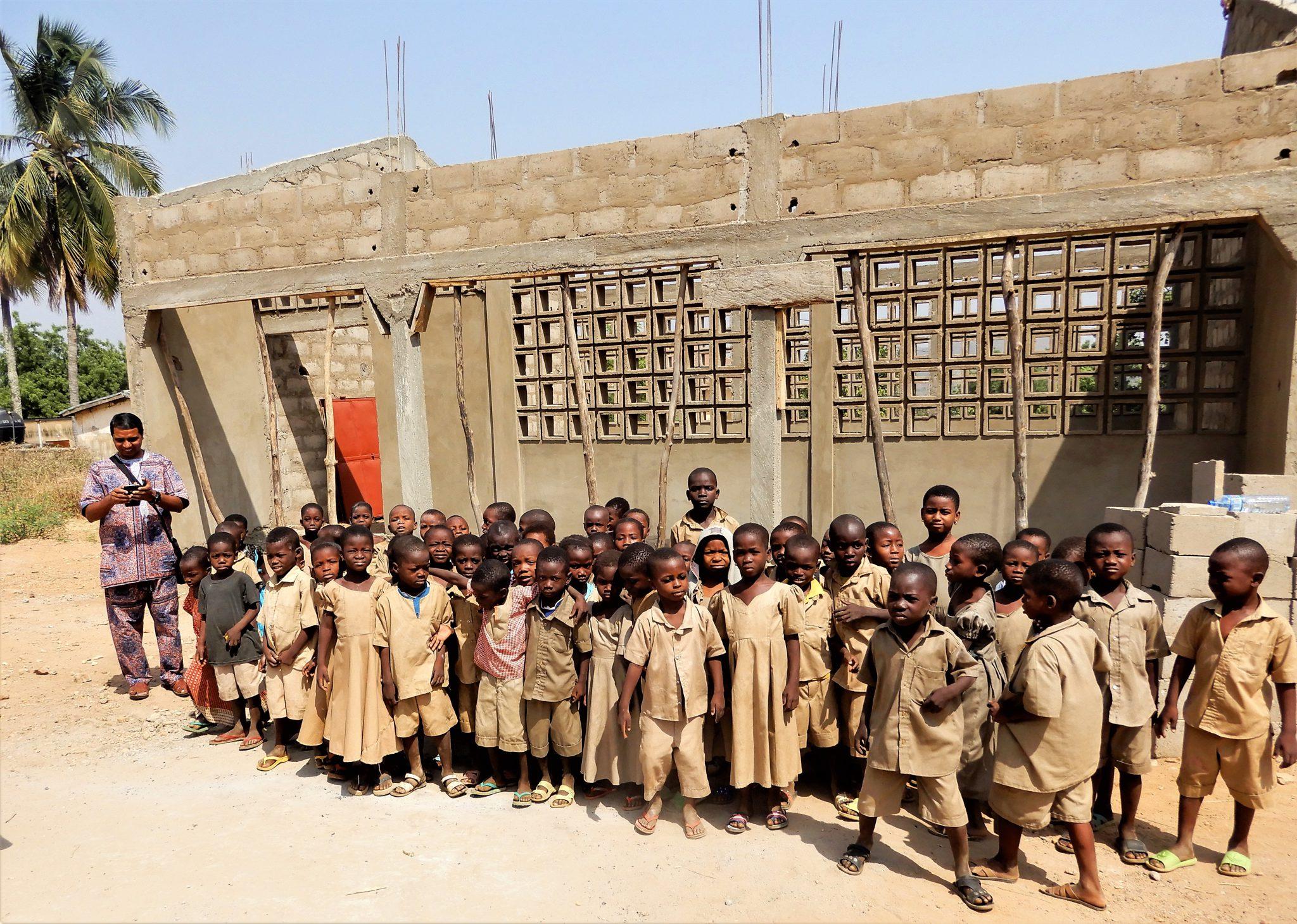 Przyszli kilkuletni uczniowie przed jeszcze nieukończoną szkołą.