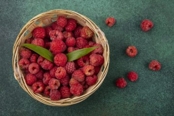 top view of raspberries with leaves in basket and on green background